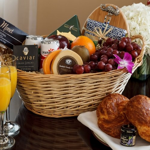 Assorted package including fruits, cheese, champagne, flowers and pastries.