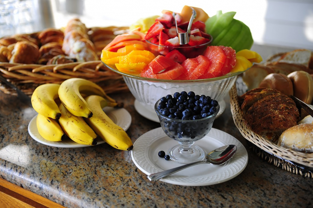Bowl of assorted fruits, next to a tray full of different breads and pastries, a plate of bananas, and bowl of blueberries.