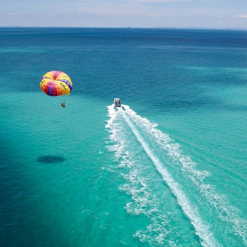 Parasailing over blue waters.