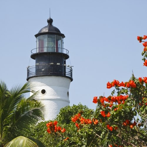 Key West Lighthouse Museum with palm trees and red flowers in the foreground.