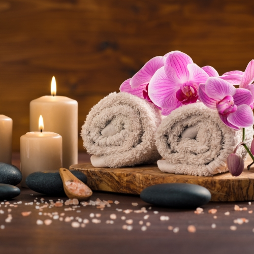 Spa setting with brown rolled towel, orchids and candles on wood. Relaxing spa concept with candles, towels and hot stone massage with himalayan pink salt.