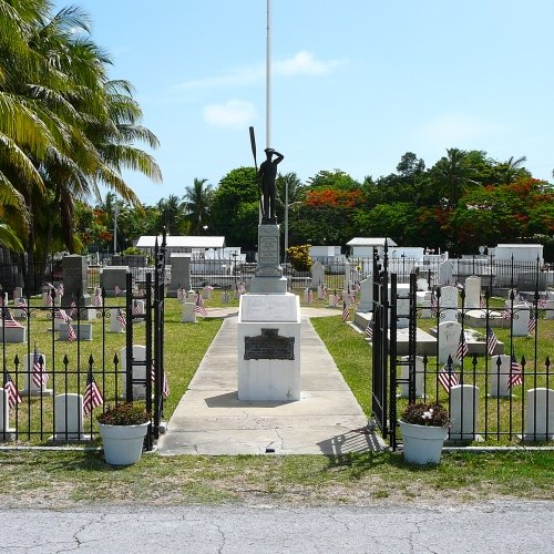 The gates and ground of Key West Cemetery with American flags on each grave.
