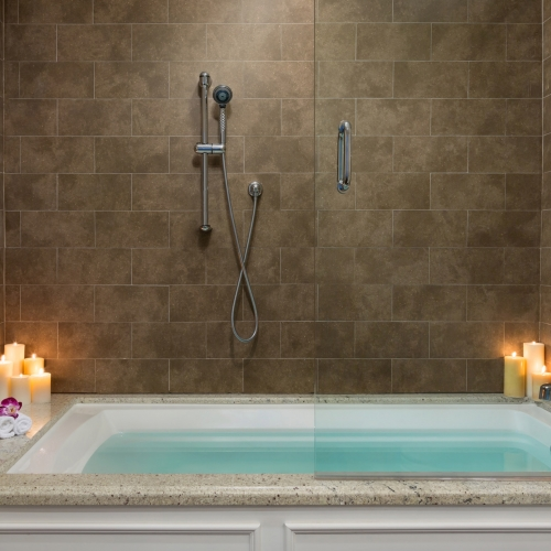 Large Jacuzzi tub lit with candles in Simonton Suite at Southernmost Beach Resort.