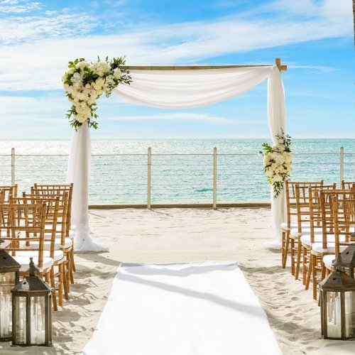 Wedding setup on the beach, including rows of white chairs, a decorated archway, and palm trees.
