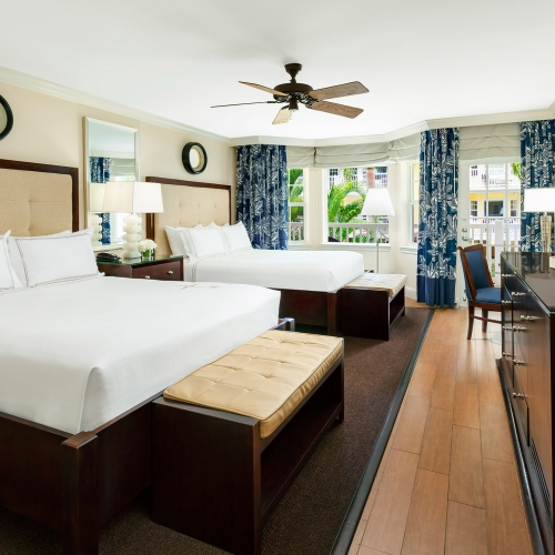 Two white beds facing a dark wooden dresser with a TV above it. Alcove window looks out at the resort.