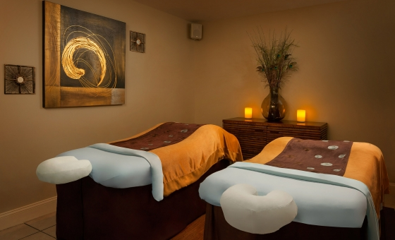Massage beds in an ambient lit room with neutral colored walls.