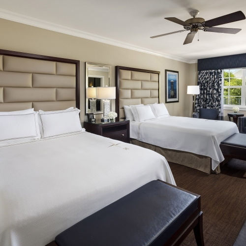 Two white beds with tan head boards. Dark brown leather benches sit at end of beds. Blue armchairs sit next to the window.