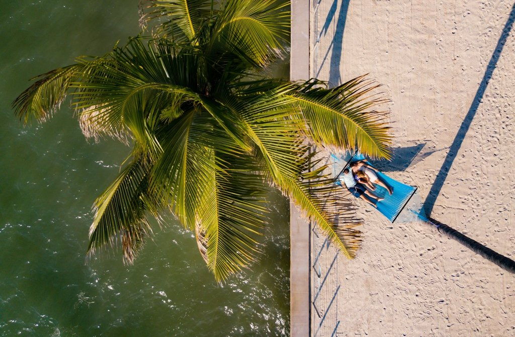 Aerial shot of couple laying in a blue hammock on the pier.