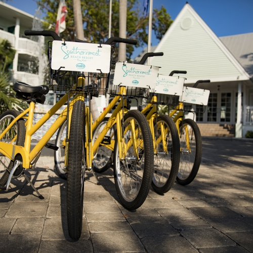Four yellow rental bikes lined up side by side with Southernmost Logo