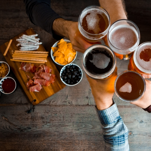 Five people cheers'ing their beers over charcuterie.