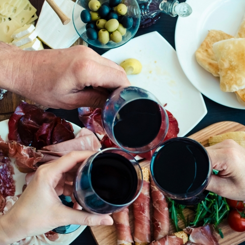 Overhead photo of three people cheers'ing their wine glasses over a charcuterie board.