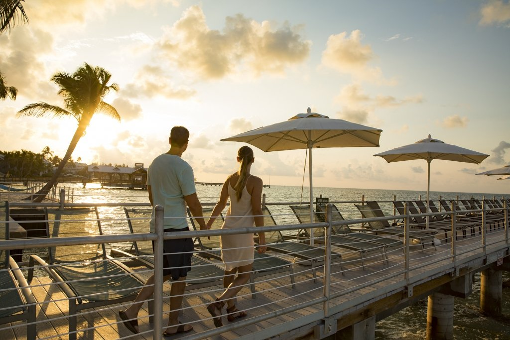Couple walking along the pier at sunset with lounge chairs arranged in a row and white beach umbrellas.