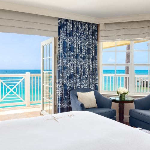 Oceanfront suite, including balcony, bed and armchairs at Southernmost suite.