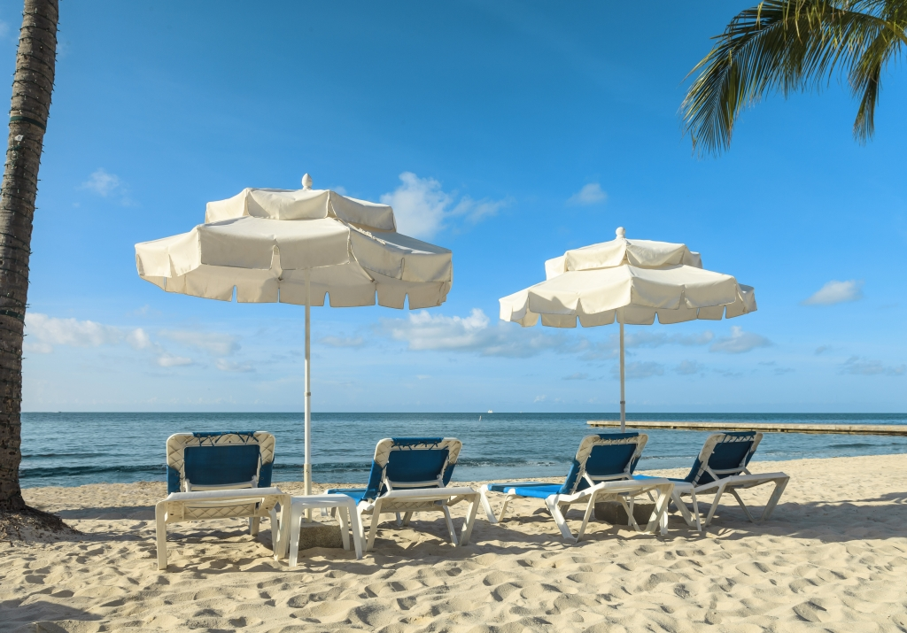 Two umbrellas and lounge chairs on the beach at Southernmost.