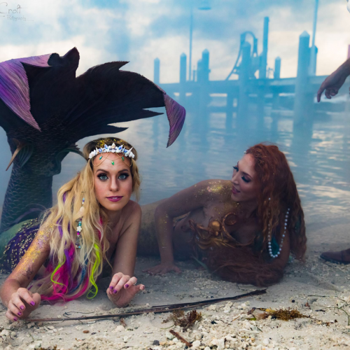 Two women dressed as mermaids pose for photo on the beach.