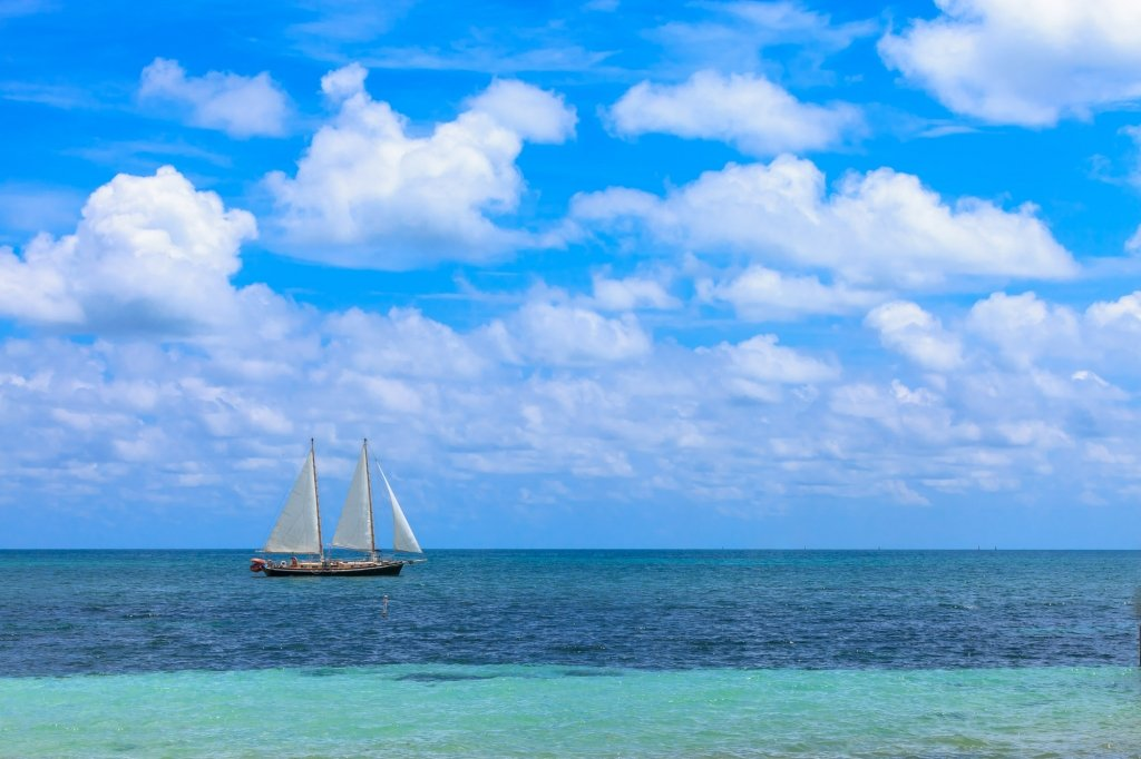 Tall ship sailing on blue waters under the sun.