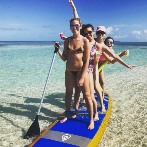 Four women posing for a photo on a blue paddleboard in shallow water with drinks in hand.