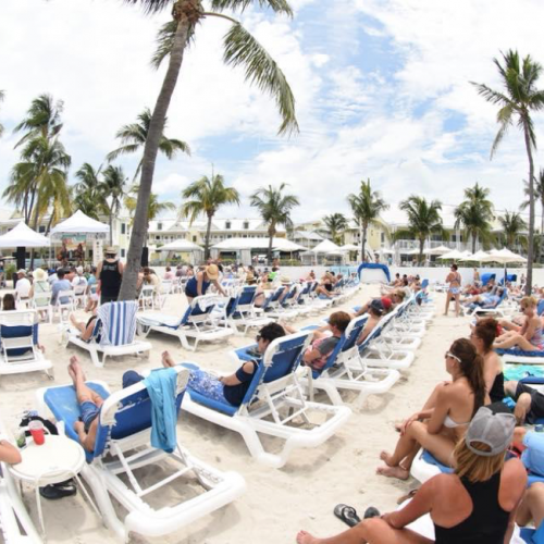 Numerous people sitting on blue and white lounge chairs listening to live music on the beach.