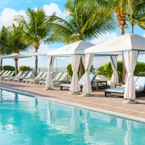 Multiple lounge chairs and white canopies lined up side by side along the edge of the pool.