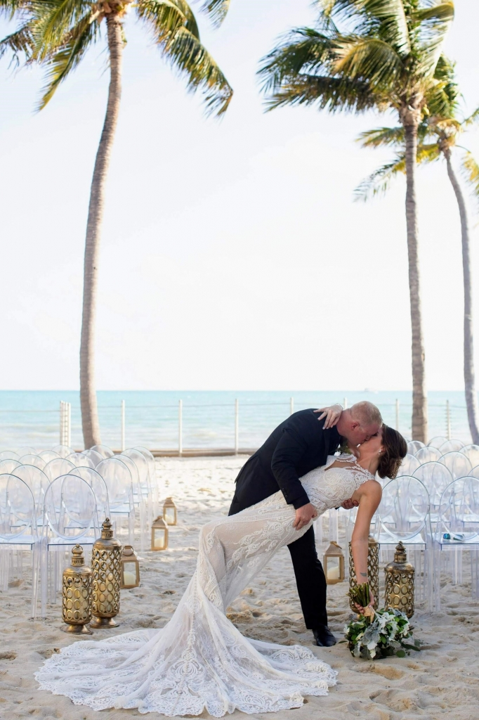 A husband dips his new bride while kissing her on the beach with clear chairs and palm trees in the background on their wedding day.