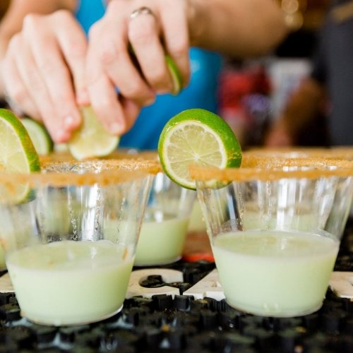 Several margaritas lined up side by side, as someone drops a lime into one of them.