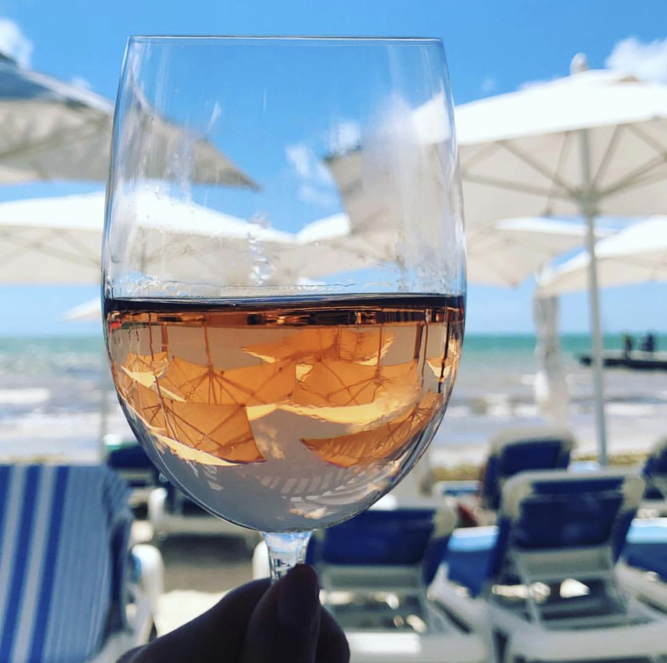 Glass of white wine being held up with white beach umbrellas in the background.
