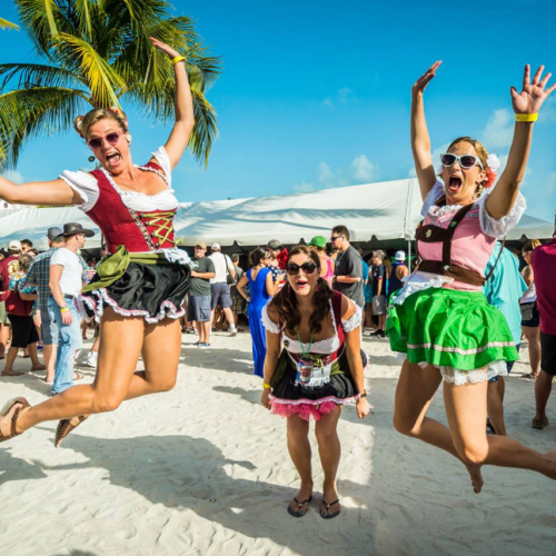 Three women jump in the air in traditional german attire on the beach.