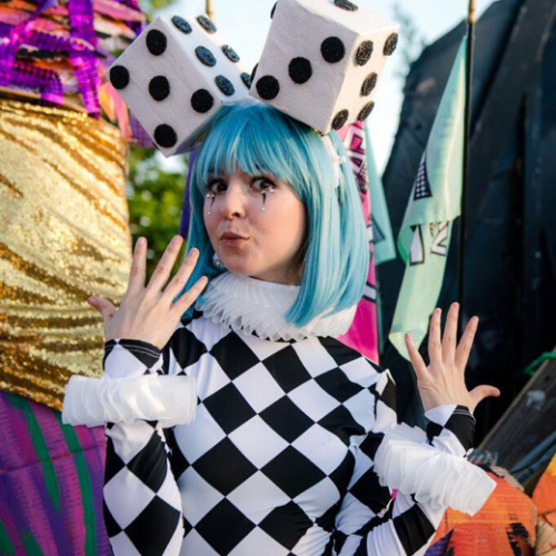 A woman posing at Fantasy Fest in costume with large dice on top of her head.