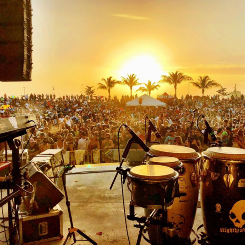 View of instruments on an outdoor stage looking into a large crowd at sunset.