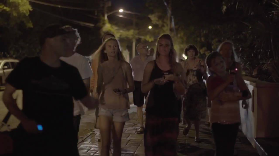 Guide leads group of tourists along dark cobble-stone road during a Haunted Key West Tour.