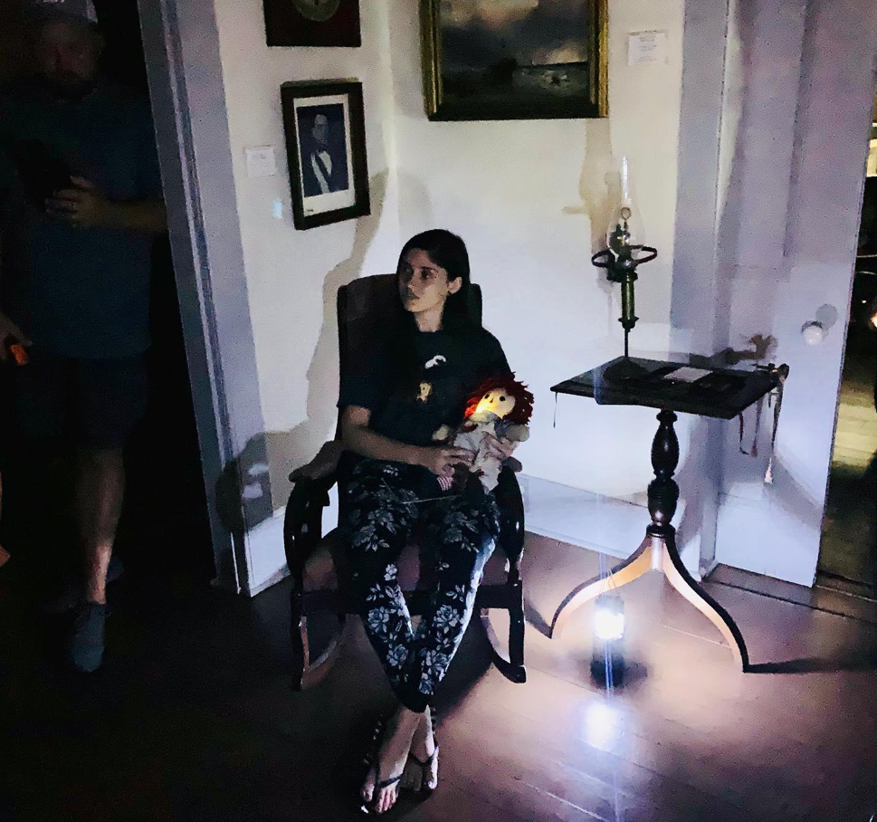 Young woman sits in a chair while holding a doll in a dimly lit room as part of the Haunted Key West Tour.