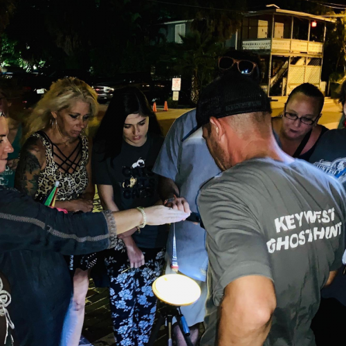 A group of people and their Haunted Key West tour guide joining their right hands in the center of a circle.