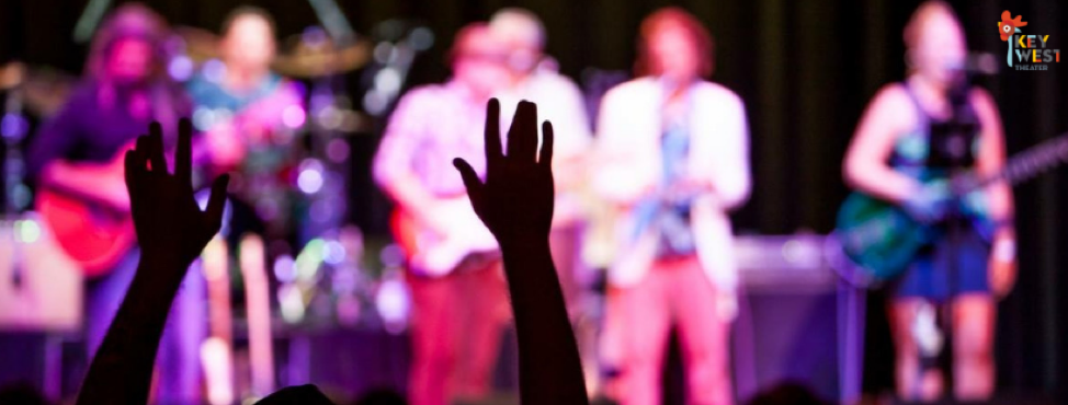Silhouette of a concert-goers hands amongst a crowd with a band on stage.