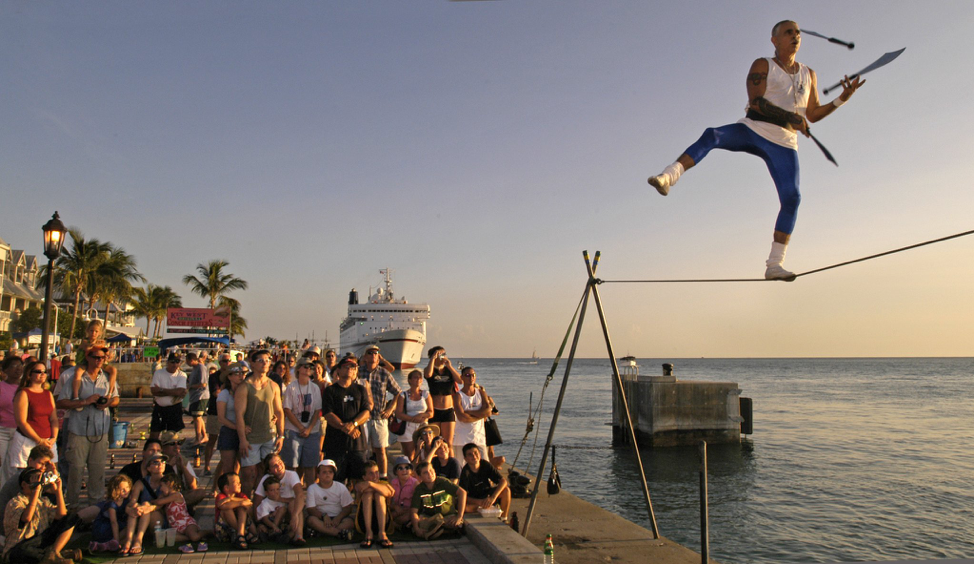 Crowd watches as performer walks along a tight rope, while juggling knives at Mallory Square.