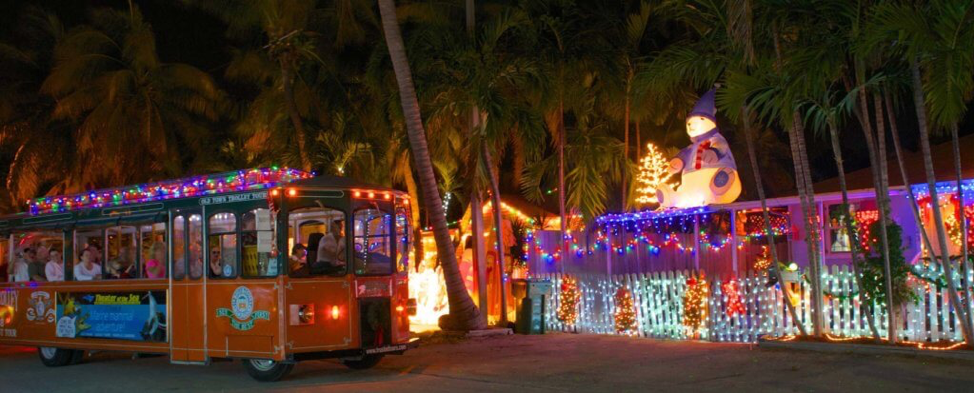 Night-time shot of a train with the Old Town Trolley Tours covered in festive lights.