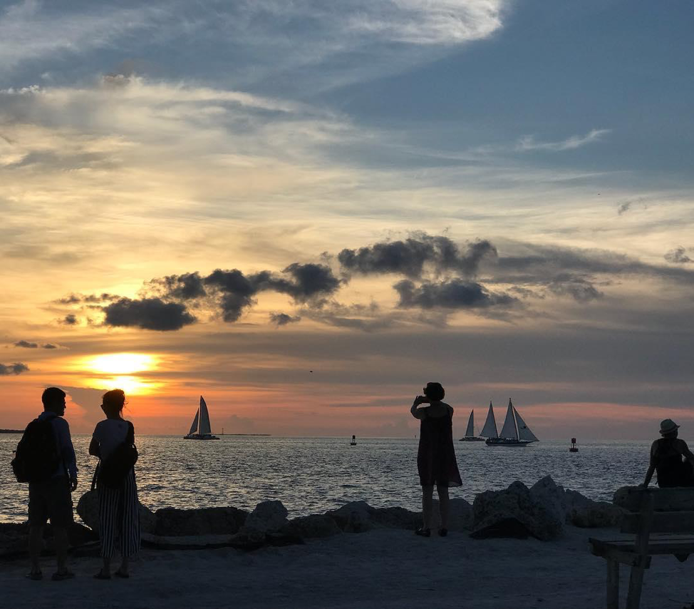 Tourists lounging and taking photos of sailboats and sunset at Fort Zachary Taylor Historic State Park.
