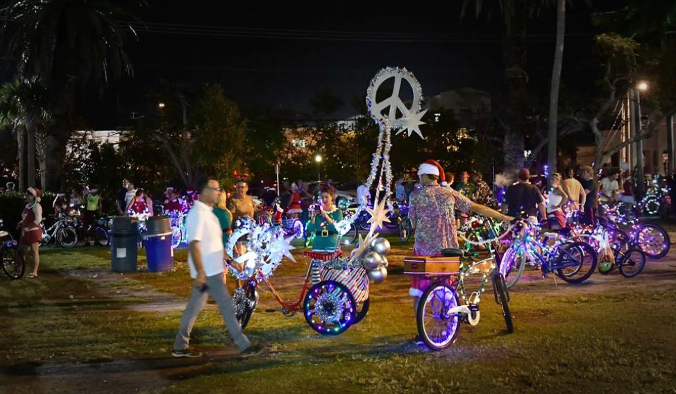 Night-time shot of participants with their decorated bicycles for the Lighted Bike Parade.