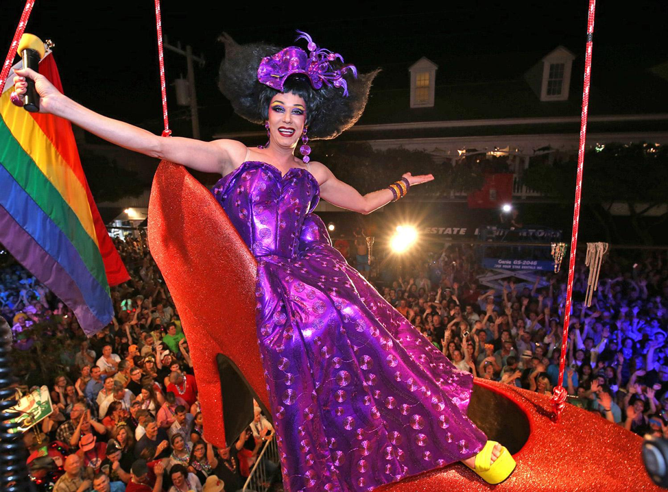 A drag queen sits in an over-sized red high-heeled shoe, suspended in the air, during a New Year's Eve performance on Duval Street.