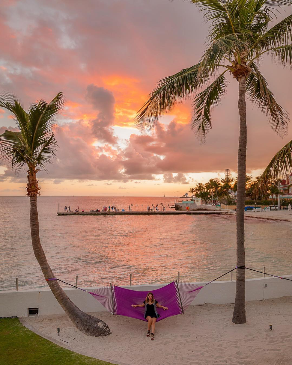 Young woman posing in a purple hammock at sunset at the Southernmost Beach Resort.