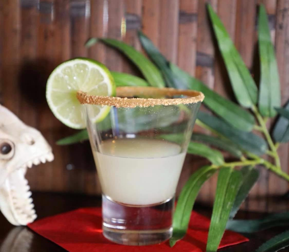 Small shot glass with key lime pie shot and lime wedge on the rim