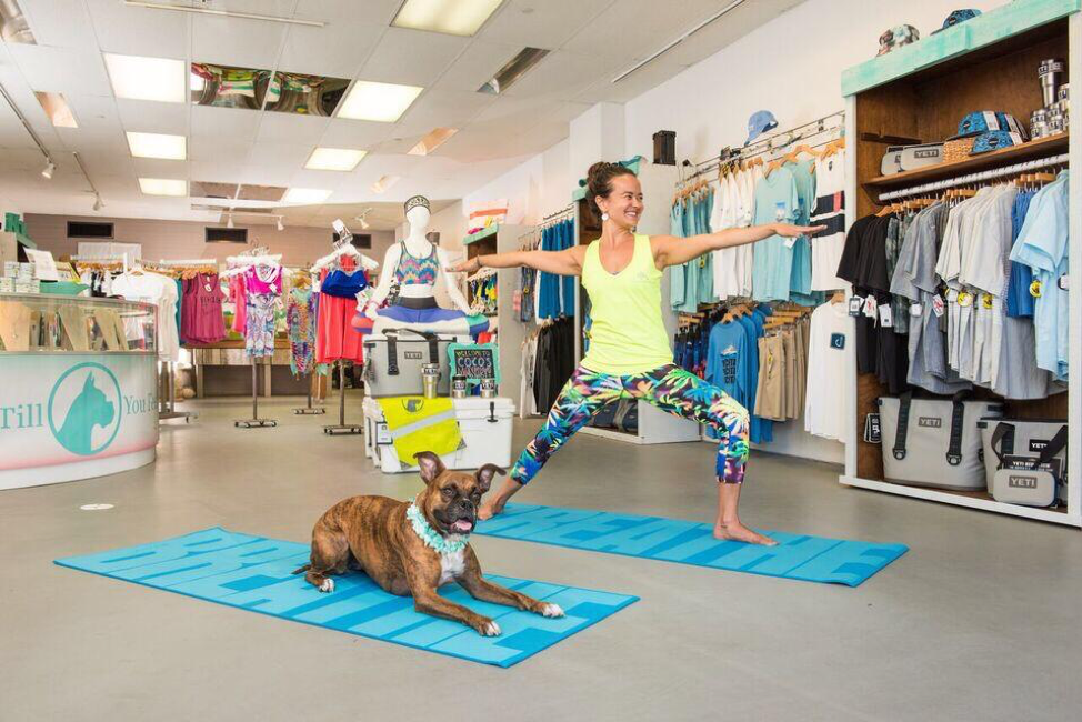 Young woman and dog do yoga inside athletic wear store.
