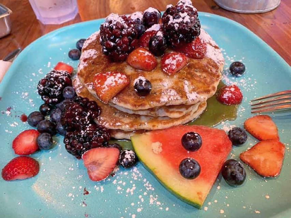 Pancakes with fresh berries and watermelon, sprinkled with icing sugar, and maple syrup