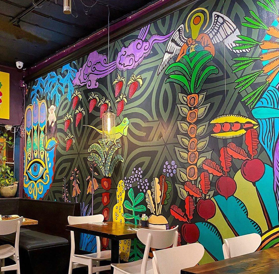 Cafe wall is painted with vibrant colors and artistic scenery