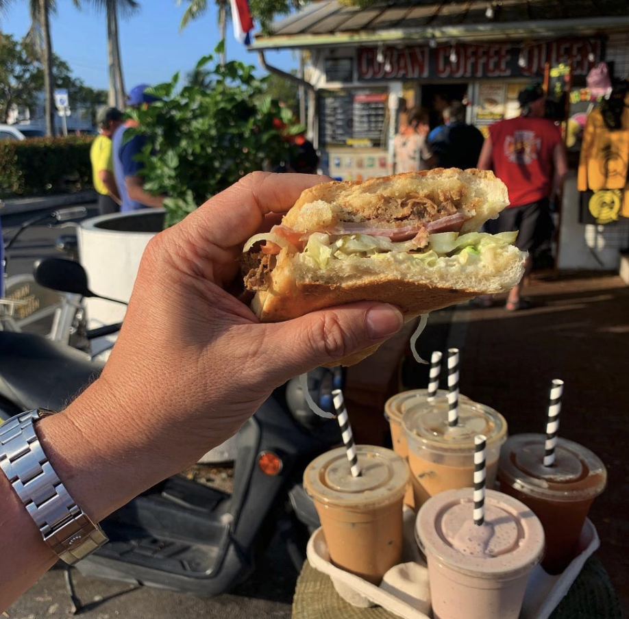 Man's hand holding Cuban sandwich with 4 milkshakes in background