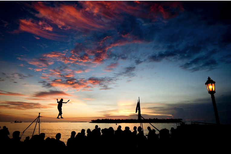 Acrobat walks a tightrope at sunset while crowd watches on