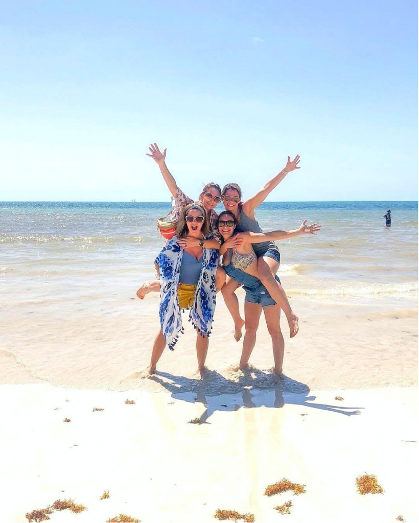 Girls posing for picture on the beach facing the camera.