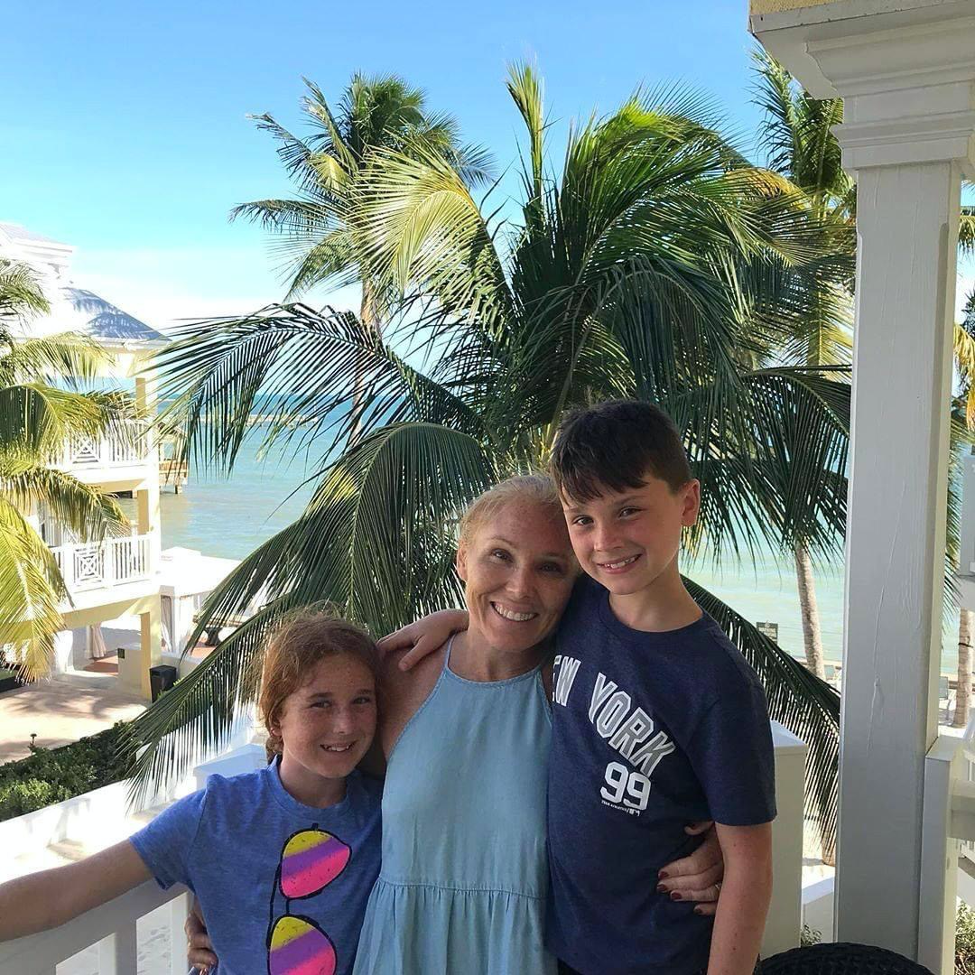 Family hugging on patio with resort backdrop.