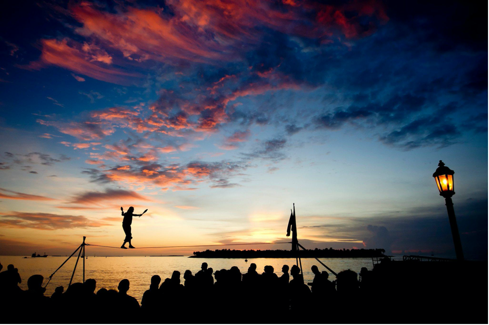 Key West Sunset by the water with man walking on tight rope.