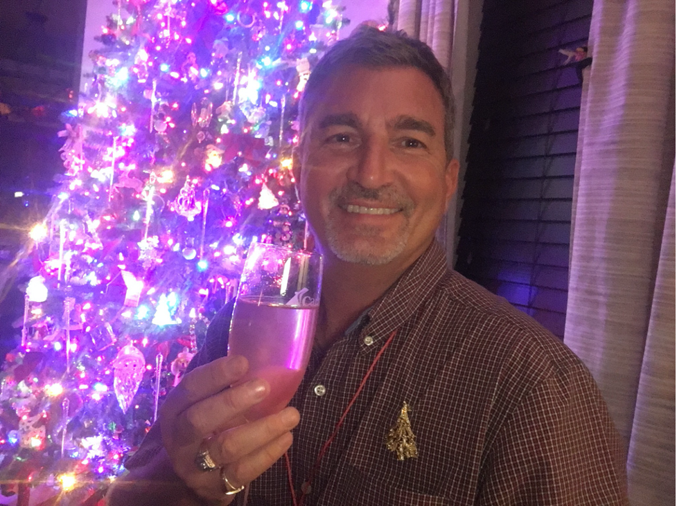 Man holding drink with decorated Christmas tree behind him