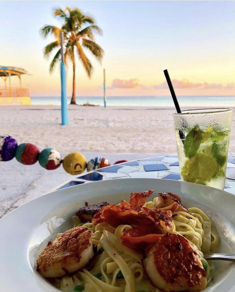 Delicious pasta dish with a tropical view of white sand, palm trees and the ocean.